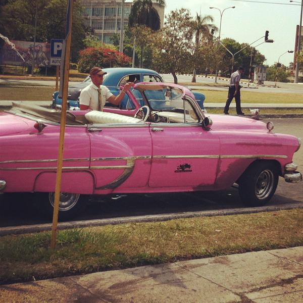 Carros antigos passam a todo instante pela cidade. Alguns donos cobram por passeios beira-mar.